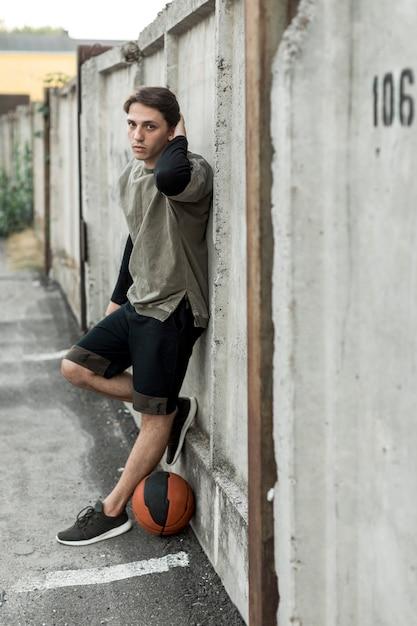 Basketteur urbain sur le côté posant Photo gratuit