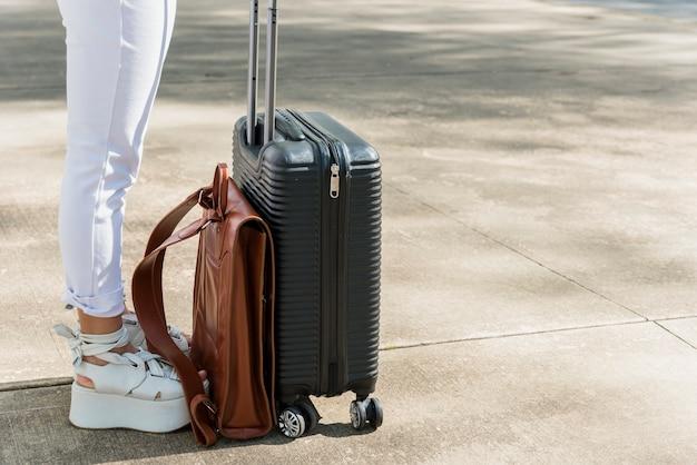 Basse section de touriste femme debout sur la route avec un sac de bagages et en cuir Photo gratuit