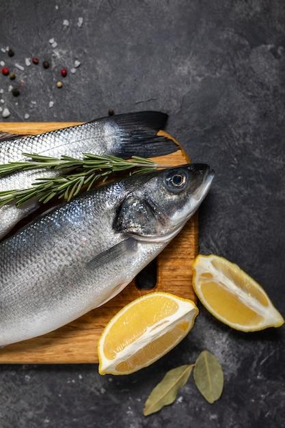 Bassin de poisson frais et ingrédients pour la cuisine, citron et romarin. vue de dessus de fond sombre. Photo Premium