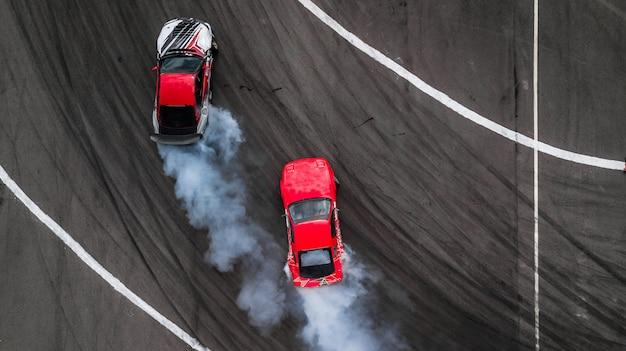Bataille de dérive vue aérienne, deux voitures dérivent bataille sur piste de course avec de la fumée. Photo Premium
