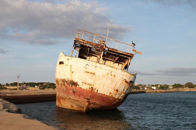 Un bateau abandonné sur le quai Photo Premium