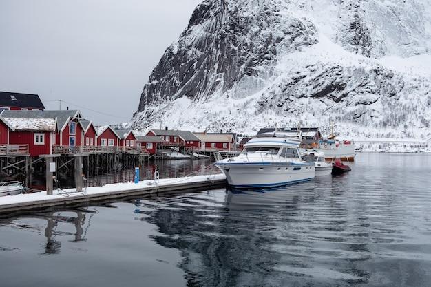 Bateau ancré sur une jetée avec un village de pêcheurs des lofoten Photo Premium