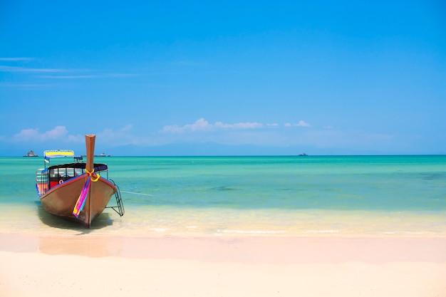 Bateau en bois sur une plage de sable blanc, plage tropicale en thaïlande Photo Premium