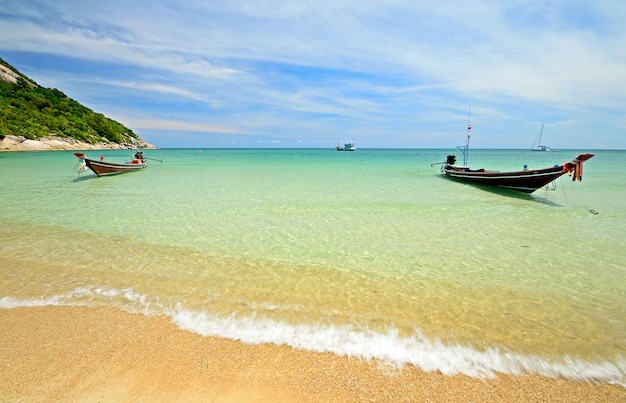 Bateau flottant sur l'eau transparente, plage turquoise de la mer tropicale en thaïlande Photo Premium