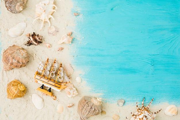 Bateau jouet et coquillages dans le sable à bord Photo gratuit