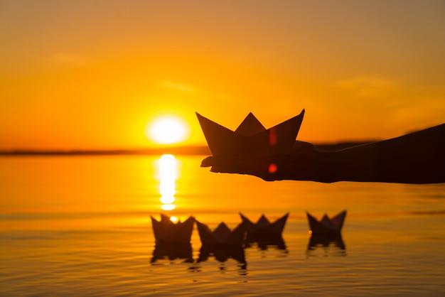 Bateau en papier est sur une paume de garçon. quatre origami en papier qui flottent dans la rivière au coucher du soleil Photo Premium