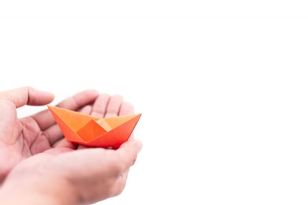 Bateau en papier orange tenant à la main sur fond blanc, concept d'apprentissage et d'éducation Photo Premium