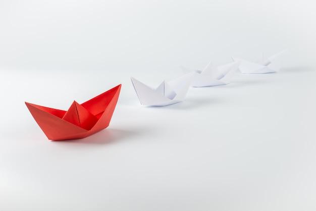 Bateau en papier rouge menant parmi les blancs Photo Premium