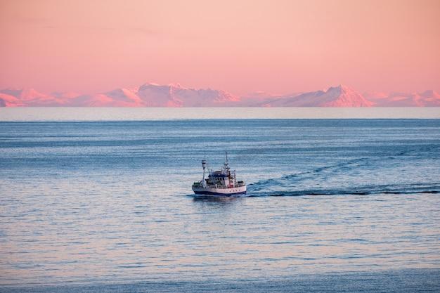 Bateau de pêche en croisière sur la mer arctique pour pêcher au coucher du soleil en hiver Photo Premium