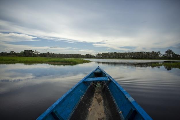 Bateau Rouillé En Bois Bleu Dans Le Lac Entouré De Beaux Arbres Verts Photo gratuit