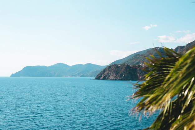 Bateaux sur l'eau bleue près du bord de mer dans le parc national des cinque terre en italie Photo Premium