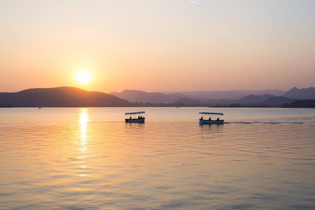 Bateaux flottant sur le lac pichola avec coucher de soleil coloré se reflétant dans l'eau au-delà des collines. udaipur, rajasthan, inde. Photo Premium