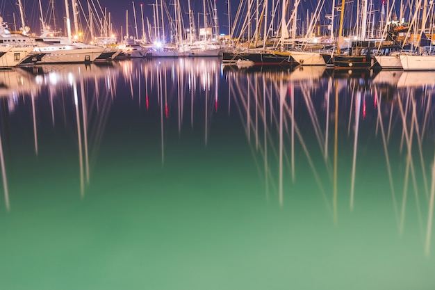 Bateaux à voile et yachts dans le port la nuit Photo Premium