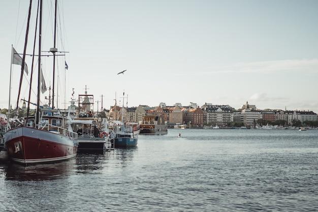 Bateaux à voile et yachts sur le quai de stockholm devant le centre-ville Photo gratuit
