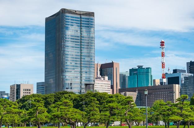 Bâtiment moderne avec jardin zen vert sur ciel bleu à tokyo, japon. Photo Premium
