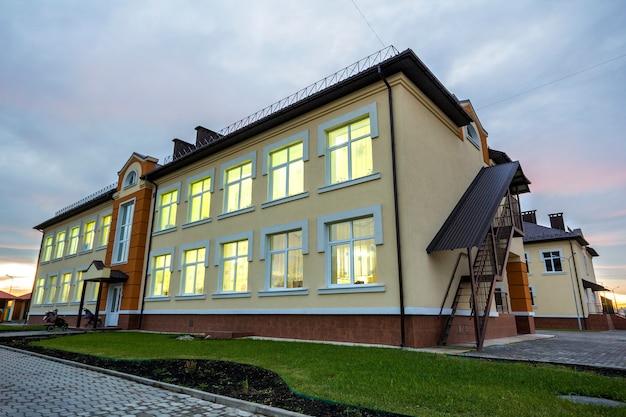 Bâtiment préscolaire de jardin d'enfants avec pelouse verte et trottoirs pavés Photo Premium