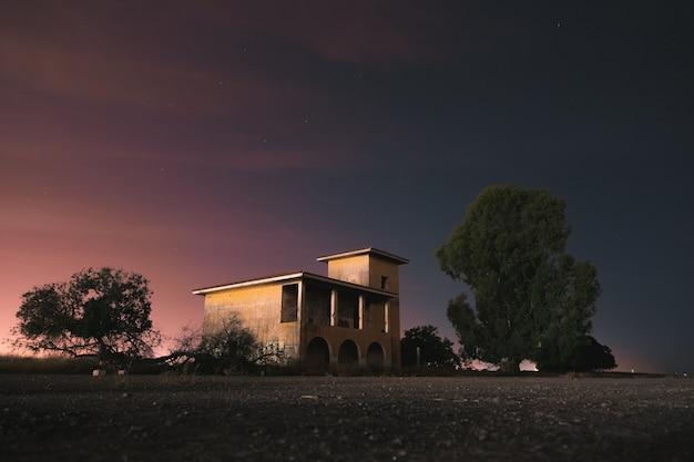 Un bâtiment solitaire et post-apocalyptique entouré d'arbres dans une nuit sombre et froide. photographie longue exposition Photo Premium