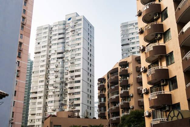 Bâtiments de grande hauteur à shanghai avec balcons et climatisation sur fond bleu Photo Premium