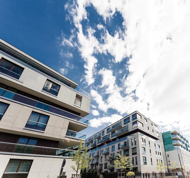 Bâtiments modernes. nouveau bloc moderne d'appartements dans la zone verte avec le ciel bleu Photo Premium