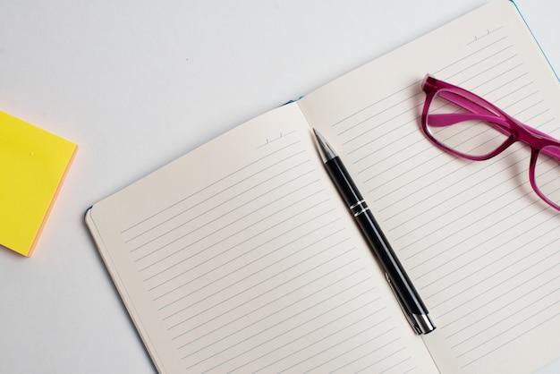 Bâton de note jaune et lunettes et stylo noir Photo Premium