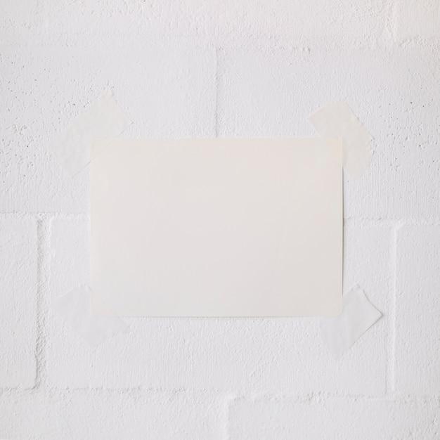 Bâton de papier vierge blanc avec du ruban adhésif sur fond de mur blanc Photo gratuit