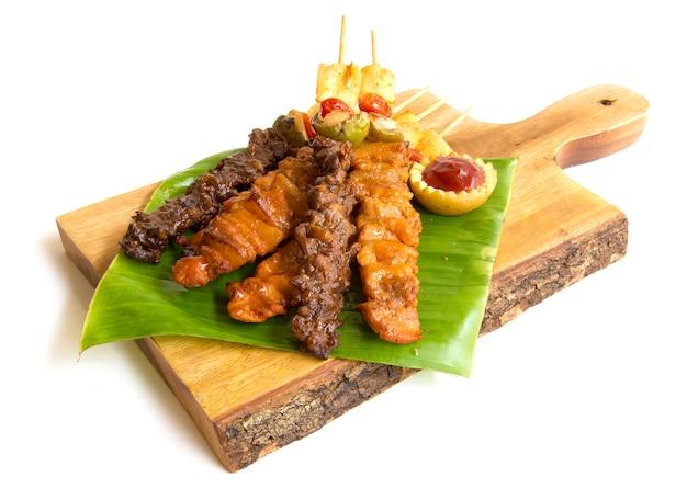 Bâton pour barbecue avec grill juteux avec sauce barbecue, style de cuisine fusion sur du bois haché Photo Premium