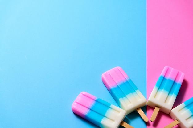 Bâtonnet de glace aux fruits, sucette glacée, glace ou congélateur sur fond pastel bleu et rose Photo Premium