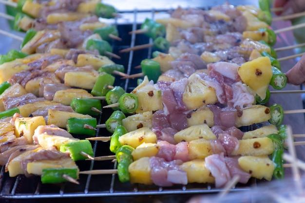 Bâtonnets de barbecue griller au feu avec de la fumée Photo Premium