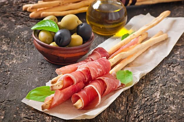Bâtonnets De Pain Grissini Au Jambon, Olives, Basilic Sur Vieux Bois Photo gratuit