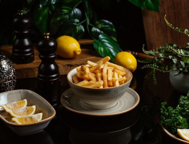 Bâtonnets de pomme de terre finement grillés servis avec des tranches de citron Photo gratuit