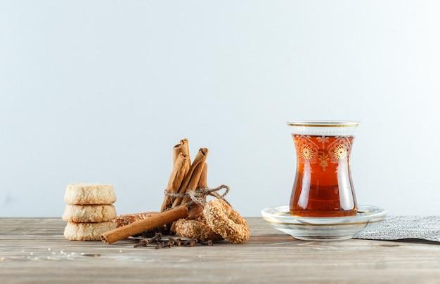 Bâtons De Cannelle Avec Biscuits, Clous De Girofle, Un Verre De Thé, Napperon Vue Latérale Sur Mur En Bois Et Blanc Photo gratuit