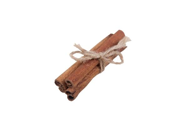Bâtons De Cannelle Isolés Sur Fond Blanc Attachés Avec Une Brindille. Concept De Nourriture Saine. Photo Premium
