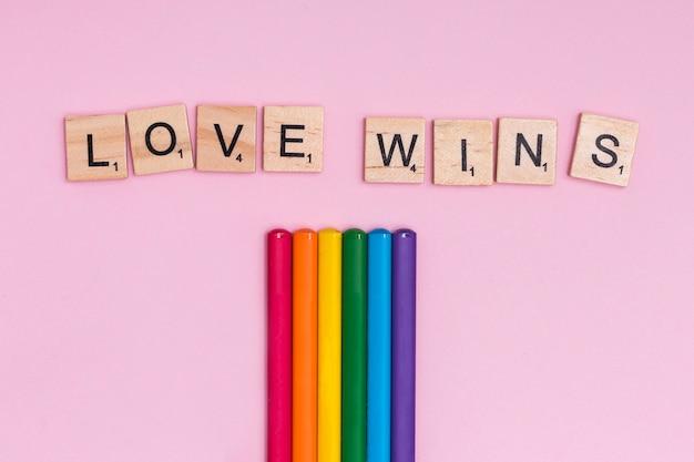 Bâtons colorés arc-en-ciel et panneau love wins Photo gratuit