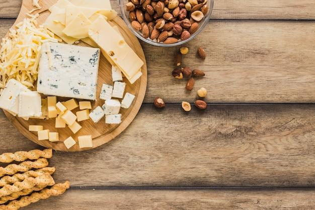 Bâtons de pain, bols de fromage râpé et d'amandes sur un bureau en bois Photo gratuit