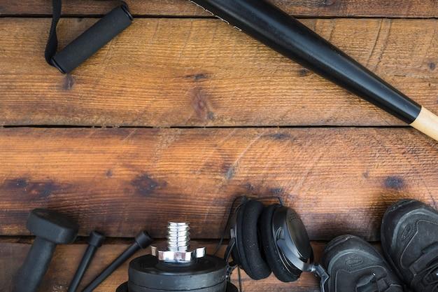 Batte de baseball; sangle de remise en forme; des haltères; corde à sauter; poids; casque et chaussures sur fond texturé en bois Photo gratuit