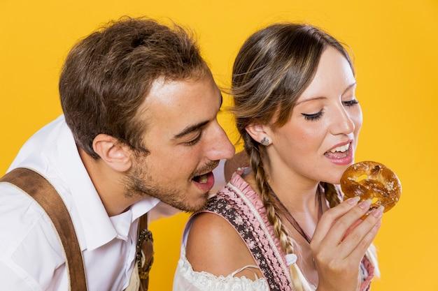 Bavarois amis mangeant un bretzel Photo gratuit