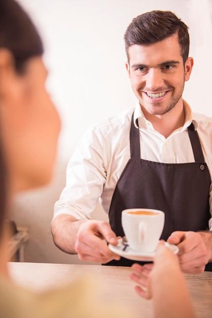 Beau barista masculin, tendant la main avec une tasse de café Photo Premium