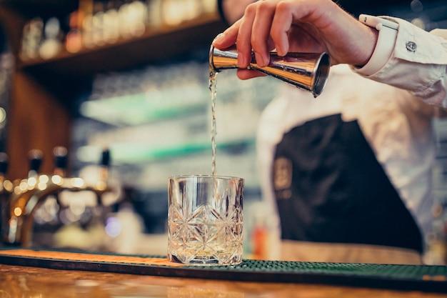 Beau Barman Faisant Boire Et Cocktails Au Comptoir Photo gratuit