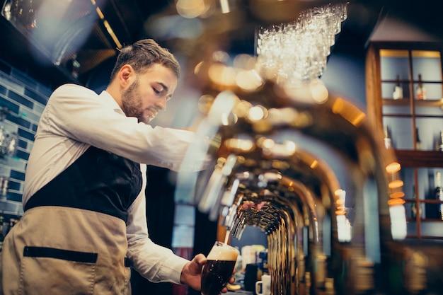 Beau Barman Versant De La Bière Au Pub Photo gratuit
