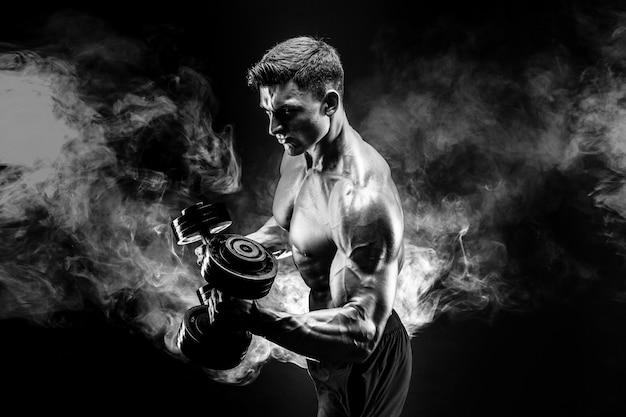 Beau Bodybuilder, Faire De L'exercice Avec Haltère. Fumée Photo Premium
