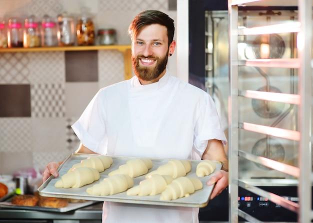 Un Beau Boulanger Avec Une Barbe Prépare Des Croissants Pour La Cuisson Et Sourit à La Boulangerie Photo Premium