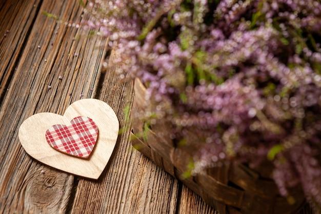 Beau bouquet frais de bruyère de la forêt en fleurs dans le symbole du panier et le coeur Photo Premium