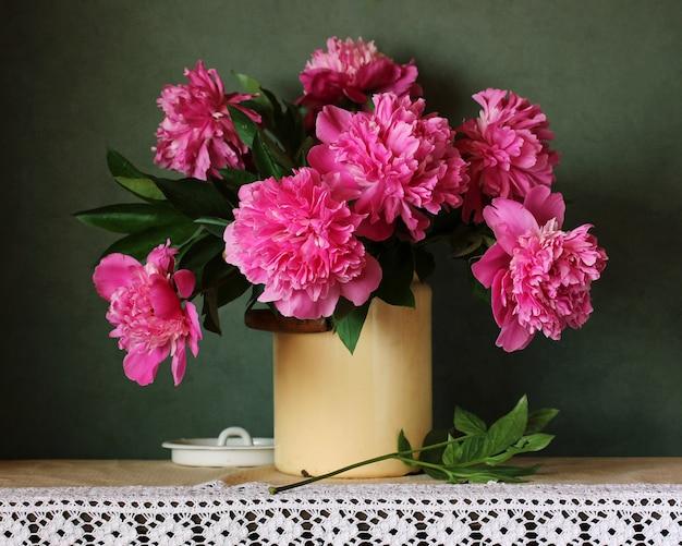 Beau bouquet de pivoines roses sur la table avec une nappe de dentelle. fleurs de jardin. Photo Premium