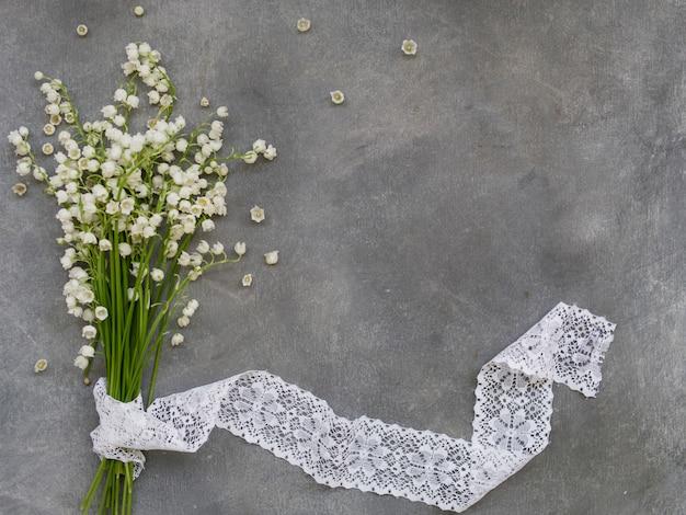 Beau cadre floral avec des fleurs de lys de la vallée sur un fond gris foncé Photo Premium