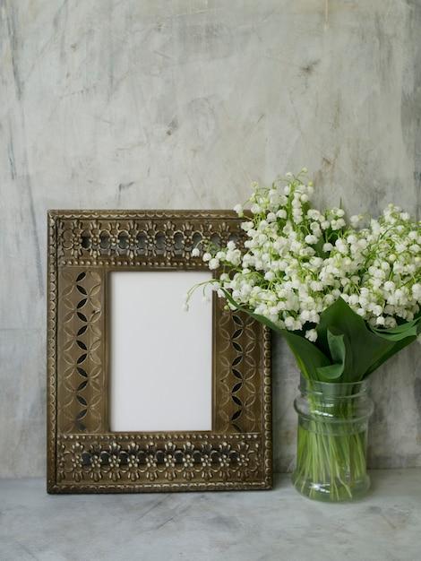 Beau cadre vintage avec bouquet de lys de la vallée sur fond gris Photo Premium