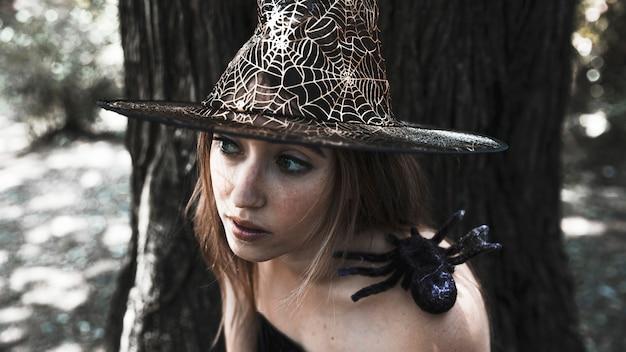 Beau Charmeur Avec Une Araignée Sur L'épaule Dans Les Bois Ensoleillés Photo gratuit