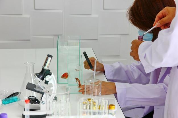 Beau chercheur en costume blanc mélange un nouveau médicament Photo Premium