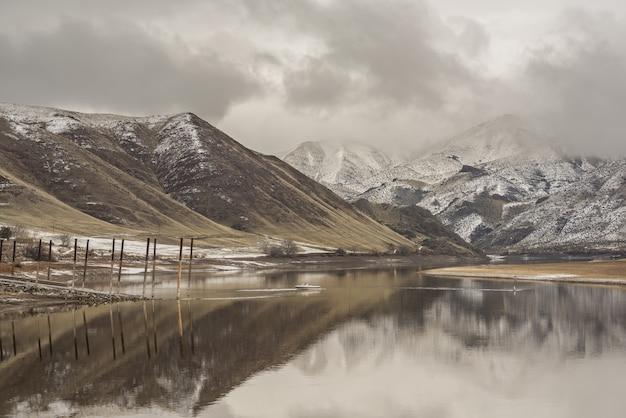 Beau Cliché De La Mer Reflétant Les Montagnes Sous Un Ciel Nuageux Photo gratuit