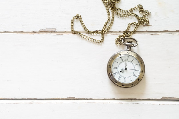 Beau collier de montre en bronze sur un plancher en bois blanc. Photo Premium