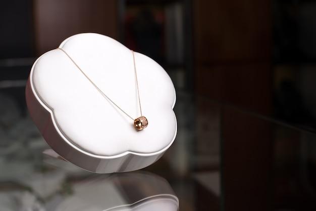 Beau Collier En Or Avec Diamants Sur Présentoir Blanc. Espace Libre Pour Le Texte. Bijoux De Luxe, Accessoires Femme En Vitrine. Photo Premium